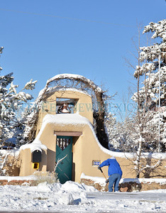 Snow is cleared in from of a home on Old Pecos Trial on a very cold Monday morning, December 10, 2012.  Clyde Mueller/The New Mexican
