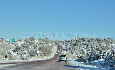 Motorists make their way along a snow and ice covered Old Las Vegas Highway on a very cold Monday morning, December 10, 2012.  Clyde Mueller/The New Mexican