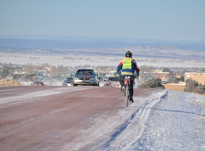 A brave cyclist makes his way along snow and ice covered Avenida Vista Grande on a very cold Monday morning in Eldorado, December 10, 2012.  Clyde Mueller/The New Mexican