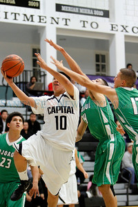 Pojoaque's Ryan Koller, number 24, and Matthew Herrera, number 12, try to block Capital's Christian Martinez, number 10, as he goes for a jump shot during the first quarter of the semifinal game between Capital High School and Pojoaque Valley High School during the Al Armendariz Classic Basketball tournament on Dec. 2, 2011, at Capital High School.  Photo by Luis Sanchez Saturno/The New Mexican
