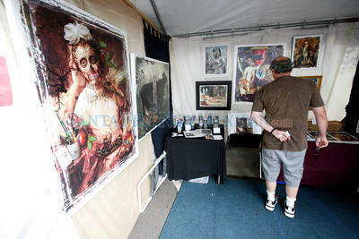 Alan Davidner, from Santa Fe, looks at prints by Alex Chavez on Lincoln Ave at Contemporary Hispanic Market on July 24, 2010, in downtown Santa Fe.                   Luis Sanchez Saturno/ The New Mexican.
