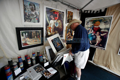 A man looks at prints by Alex Chavez on Lincoln Ave at Contemporary Hispanic Market on July 24, 2010, in downtown Santa Fe.                   Luis Sanchez Saturno/ The New Mexican.