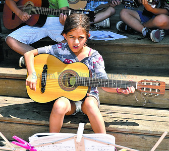 "Emma Reynolds, 8 year old student at El Dorado Community School strums her guitar and sings, ""He's Got The Whole World in His Hands"" along with other students enrolled in the Santa Fe Public Schools' summer music camp program led by teacher Brandelyn Davidson play their guitars and sing for passersby's at 11 a.m. at the Santa Fe Plaza Band Stand on Friday, June 22, 2012. Clyde Mueller/The New Mexican"