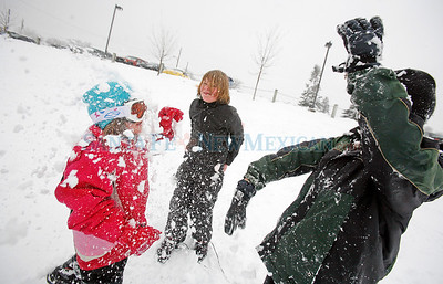 Nick Selinger, 11, center, and Christian Herrera, 10, right, team up on Christian's sister, Maya Herrera, 6, left, all from Santa Fe, during a snow ball fight at Alto-Bicentenial Park on Jan. 28, 2010.           Luis Sanchez Saturno/ The New Mexican.