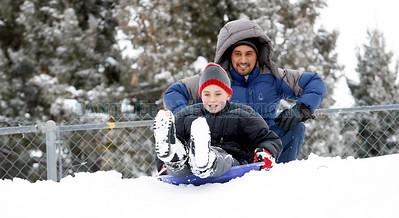 (L-R) Harsimran Khalsa and Datta Khalsa sled down a hill near their home in Santa Fe, N.M. on Jan 20, 2010.  Natalie Guillen/The New Mexican
