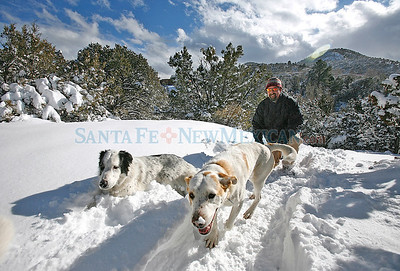 Charlie Paynter takes a walk with his dog, left,Tonka and Quinnie at Atalaya on Tuesday, December 23, 2008. Photos by Jane Phillips/The New Mexican No Published Caption