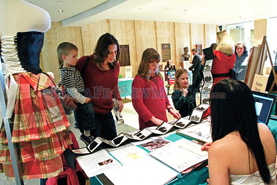 From left, Fashion student, Paola Palacios,20, speaks with Heather Doyle and her children, Uriah,3, Sarah,11, and  Grace,7, during the Santa Fe Community Collage Day at the Capitol on Thursday, February 7, 2013.  Doyle's daughter, Sarah, is interested in designing shoes.  Jane Phillips/The New Mexican