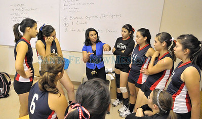 McCurdy Charter School head coach Anita Rodriguez, center, gives a speech to the Lady Bobcats before facing Dulce in a match Tuesday night in Memorial Gymnasium. The Lady Bobcats were 2-1 on the season going into Tuesday's match. McCurdy  High -vs- Dulce girls varsity volleyball match played at McCurdy, Tuesday, September 18, 2012. Clyde Mueller/The New Mexican